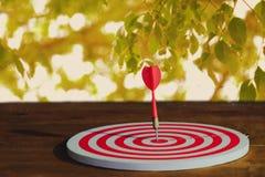 Arrow on dart board paint light stock photography