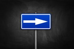 Arrow directional sign on dark black wall Royalty Free Stock Images