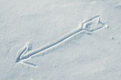 Arrow drawn on a snow Stock Photos