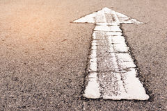 An arrow. Grunge white arrow on surface of traffic  road Royalty Free Stock Photos