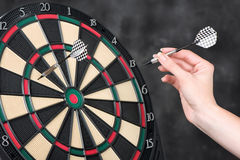 Arrow in hand and dartboard Stock Photography