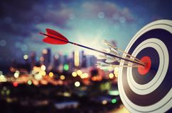 Arrow hit the center of target with modern skyline background. Business target achievement concept. 3D Rendering. Target hit in the middle by arrow. Business stock illustration