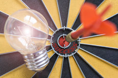 Arrow hitting the success bullseye target with idea lamp on dart Royalty Free Stock Photography