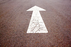 Arrow Indicating Straight On Tarred Road Surface. White painted arrow indicating straight on tarred road surface Royalty Free Stock Photography
