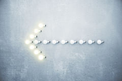 Arrow left of glowing lightbulbs on concrete wall. Close up stock photos