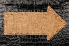 Arrow made of burlap lies on a crocodile skin Stock Image