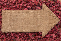 Arrow made of burlap lies on dried cranberries Stock Images