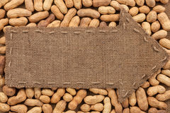 Arrow made of burlap lies on peanuts Royalty Free Stock Photography