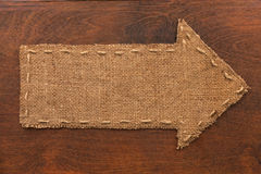 Arrow made of burlap lies on a wooden background Stock Image