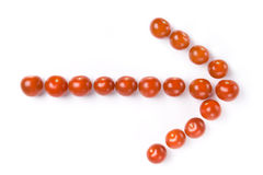 Arrow made of cherry tomatoes. On the white background Stock Photography
