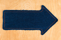 Arrow made of jeans  lies on a wooden background Royalty Free Stock Photo