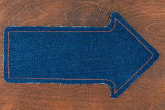 Arrow made of jeans lies on a wooden background Stock Photos