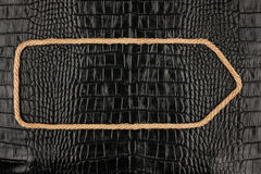 Arrow made of rope  lies on a background of crocodile  leather Stock Images