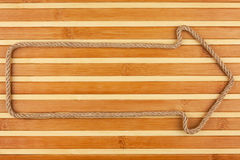 Arrow made of rope  lies on a bamboo mat Royalty Free Stock Photo