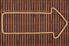 Arrow made of rope  lies on a bamboo mat Royalty Free Stock Images