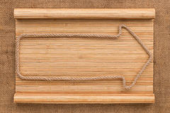 Arrow made of rope lying on a bamboo mat in the form of a manuscript Royalty Free Stock Photography