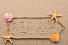 Arrow made of rope and sea shells with the word relax on the san Royalty Free Stock Photo