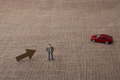 Arrow and a man figurine and a red toy car. A canvas background Royalty Free Stock Photos