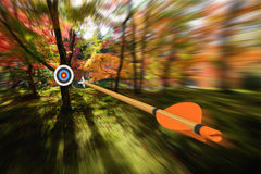 Arrow moving with precision and blurred motion toward an archery target, part photo, part 3D rendering Stock Photos