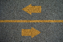 Arrow opposite directions on the on Asphalt roads Royalty Free Stock Image