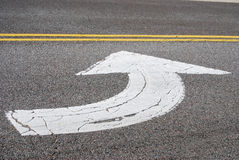 Arrow Painted On Asphalt Street. A photograph of a white traffic arrow and yellow lines painted on the asphalt street stock image