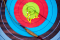 The arrow pierced the center of the paper target of concentric circles of different colors. Stock Image