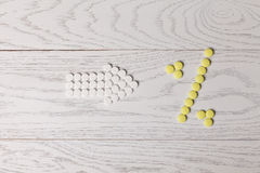 Arrow of pills point to percent of pills on table Royalty Free Stock Photography