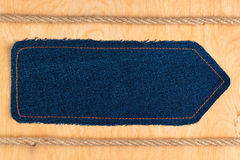 Arrow pointer is made of denim and two ropes, lie on a wooden surface Stock Photos