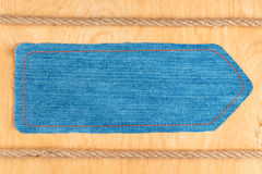 Arrow pointer is made of denim and two ropes, lie on a wooden surface Royalty Free Stock Photo