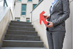 Arrow pointing to stairs upwards. Red arrow pointing the way to stairs upwards Stock Photo
