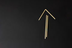 Arrow pointing up is made of raw macaroni Royalty Free Stock Photography