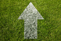Arrow pointing up symbol on grass Royalty Free Stock Images