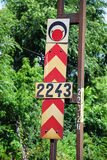 Arrow and red light signs next to a railway track Stock Image