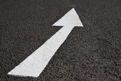 Arrow on road. White painted directional arrow on asphalt road Stock Image