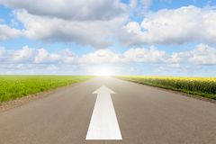 Arrow on the road. Between fields with blue sky and clouds Stock Image