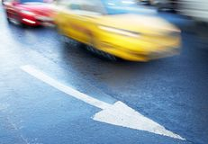 Arrow on the road and moving cars Royalty Free Stock Photos