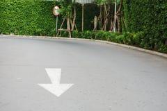 Arrow on road near convex mirror. Arrow on road near street corner with convex mirror Royalty Free Stock Images