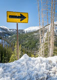 Arrow road sign in mountain winter scenery Royalty Free Stock Photo