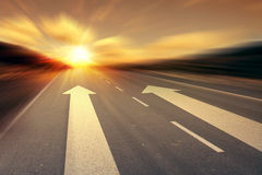 Arrow on the road. With sunrise background Royalty Free Stock Image
