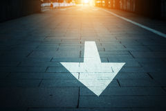Arrow on the road. When sunset Royalty Free Stock Image