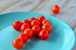 Arrow shape of Cherry tomatoes on a turquoise plate Royalty Free Stock Images