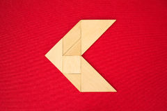 Arrow showing direction. Flat lay - geometrical abstract background or arrow showing direction made of wooden tangram pieces. Unicolor background made of red stock photos