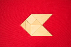 Arrow showing direction. Flat lay - geometrical abstract background or arrow showing direction made of wooden tangram pieces. Unicolor background made of red stock images