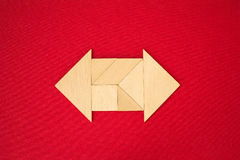 Arrow showing direction. Flat lay - geometrical abstract background or arrow showing direction made of wooden tangram pieces. Unicolor background made of red royalty free stock image