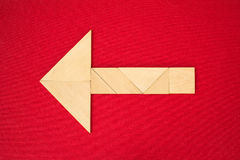 Arrow showing direction. Flat lay - arrow showing direction made of wooden tangram pieces. Unicolor background made of red fabric texture. Vignetting stock image