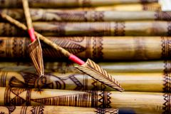 Arrow showing hand made wooden bamboo carving engraved fish figure artwork on bamboo, rows of engraved bamboo sticks. tribal artwo Royalty Free Stock Photo