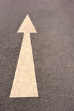 Arrow sign on asphalt road. Royalty Free Stock Photo