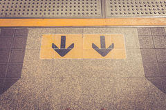 Arrow sign on floor at the sky train Royalty Free Stock Images