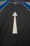 Arrow sign pointing forward. On empty parking road Stock Images
