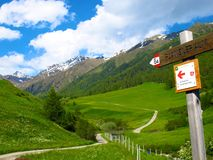 Arrow sign points towards Alpine walking trail to Planeiler Alm. An arrow along a walking trail in an Alpine valley in South Tyrol, Italy points to Planeil Alm Stock Images